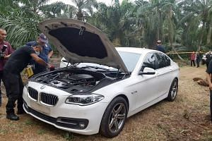 Police officers collecting evidence from the white BMW that was used in the murder at a petrol station in Johor Baru, at an oil palm estate in Pontian on Dec 26, 2017.