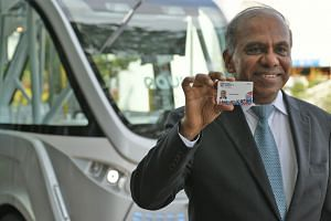 New NTU president Subra Suresh with the smart pass that all NTU students will receive in the next few weeks. It can be used to make cashless payments in the canteen or to check out books from the library, among other things. Behind him is a driverles