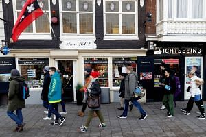 People walk past a tourist shop in central Amsterdam, Dec 1, 2017.