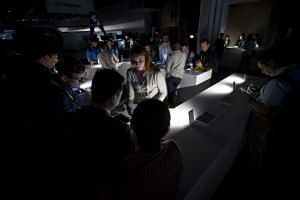 A Huawei Technologies representative assists attendees during the power outage.