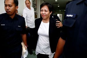 Police officers escorting Australian Maria Elvira Pinto Exposto to a court in Shah Alam, Kuala Lumpur, on Dec 27, 2017.
