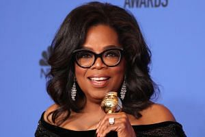 Oprah Winfrey poses with her Cecil B. DeMille Award at the Golden Globes.