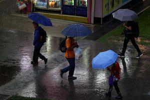 Pedestrians near Jurong East MRT Station holding umbrellas as they walk in the rain on Jan 11, 2018.