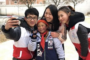 "Volunteers with eight-year-old Wang Fuman after helping him put on a pair of gloves. Donations, including winter clothing and heaters for his school in Yunnan, have poured in since his ""Snowflake Boy"" photo went viral."