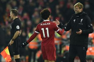 Liverpool's German manager Jurgen Klopp (right) greets Liverpool's Egyptian midfielder Mohamed Salah as he comes off during the English Premier League football match between Liverpool and Manchester City at Anfield in Liverpool on Jan 14, 2018.