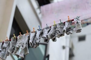 Socks hang on a clothesline in Clementi, as warmer weather sets in, on Jan 16.