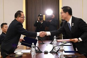 South Korean chief delegate Chun Hae Sung (right) shaking hands with North Korean chief delegate Jon Jong Su as they exchange joint statements during their working-level talks.