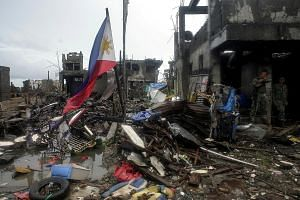 A Philippine flag seen among destroyed houses in Bangolo town in Marawi city last October. A war broke out between government troops and Muslim militants in Marawi in May, and raged on till late October. The conflict rekindled long-simmering tensions