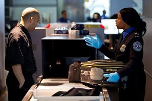 A TSA security agent checking a passenger's luggage in New York in a file photo.