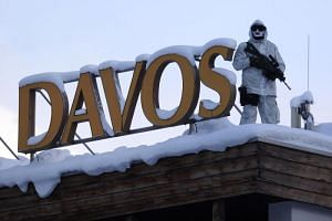 An armed member of the Swiss Police watches from the roof of the Hotel Davos ahead of the World Economic Forum (WEF) in Davos, Switzerland, on Jan 16, 2017.