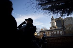 Tourists wait in line to see the Liberty Bell in front of the shuttered Independence Hall in Philadelphia after the government shutdown on Jan 20, 2018.