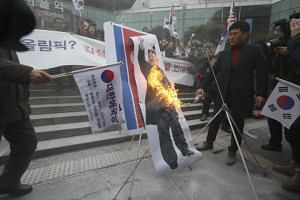 Protesters burn an image of North Korean leader Kim Jong Un during a rally against North Korea's participation to the Pyeongchang Winter Olympics in Seoul on Jan 22.