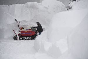 A man using a snow blower to clear a path through Davos, on Jan 22, 2018.