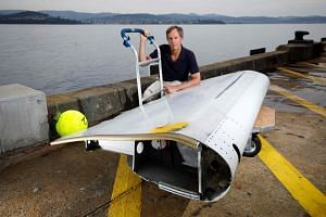 CSIRO oceanographer David Griffin posing with a Boeing 777 flaperon, used for drift modelling in the search for Malaysia Airlines' flight MH370 that went missing in 2014, in Hobart.