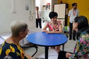 Ms Indranee Rajah with two seniors at the AWWA Senior Community Home in Ang Mo Kio.