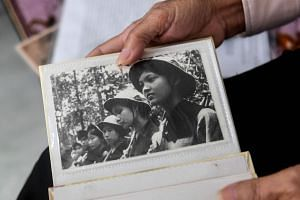 Hoang Thi No shows a photograph of Perfurme River squad members in Vietcong uniform during an interview with AFP at her home in Hue, Vietnam, on Jan 17, 2018.