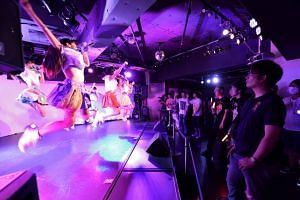 Adults watching a concert by an idol group in Tokyo. Rights groups have complained that society's sometimes permissive view of the sexualisation of young girls puts minors at risk.