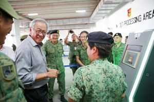 Defence Minister Ng Eng Hen being introduced to the machines used to process incoming and outgoing personnel during the mobilisation. ST PHOTO: ONG WEE JIN