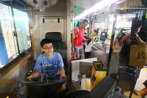 Jeroy Seng, 12, in the driver's seat of the MAN A95 three-door SBS Transit bus at the Seletar bus depot carnival yesterday. SBS Transit will expand its bus service network in the Ang Mo Kio and Yishun areas in two months' time.