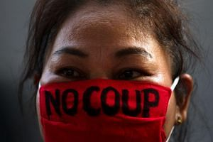 A pro-democracy protester wearing a face mask with a written message, takes part in a protest against junta delaying polls in Bangkok, Thailand on Jan 27, 2018.
