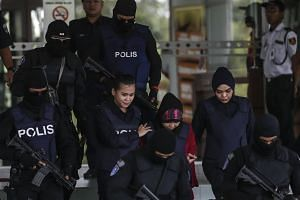 Indonesian Siti Aisyah, who is detained in connection with the death of Kim Jong Nam, is escorted by Malaysian police officers as they leave the Shah Alam High Court on Jan 22.