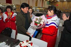 North Korean female ice hockey player Jin Ok (right) receives flowers from Lee Jae-Geun (centre), head of South Korea's national training centre, to celebrate her birthday in Jincheon on Jan 28, 2018.