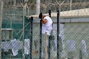A Guantanamo Bay detainee does pull-ups inside an exercise area at the detention facility.