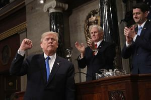 US President Donald Trump gestures at the podium in front of US Vice-President Mike Pence (top, left) and Speaker of the House Paul Ryan.
