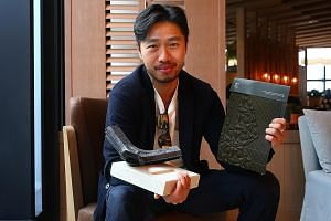 Mr Arthur Huang's upcycling company has created 1,200 new materials from trash. In his right arm is a concrete-like building material made from 2,000 cigarette butts. Sitting on it are air filters made from old clothes. The piece of fabric in his lef
