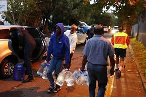 Cape Town residents collecting drinking water from a mountain spring collection point.