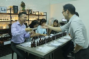 Customers creating their own perfumes at Oo La Lab. (Above) Mr Jason Lee of Six creates perfumes that embody a travel experience. (Left) Ms Gauri Garodia's Code Deco offers 17 fragrances. Mr Jason Lee of Six creates perfumes that embody a travel expe