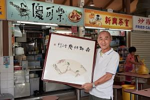 Mr Tan Kin Chwee showing a calligraphy and painting artwork created by three artists - Chen Xiang, Wang Wing Seung and Chao Shao An - in front of his noodle stall in Sembawang Hills Food Centre. Mr Tan donated 44 of Chao's artworks to the Guangzhou M