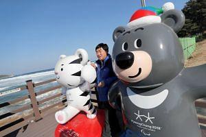 A man poses with the 2018 Pyeongchang Winter Olympics and Paralympics mascots Soohorang and Bandabi at the beach in Goseong, South Korea.