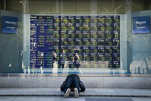 The sell-off on Wall Street sent markets in the region, including Tokyo (above), into turmoil yesterday. In Singapore, there was