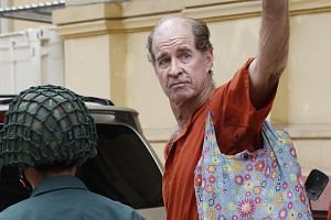 Australian filmmaker James Ricketson (right) being escorted by Cambodian police officers while arriving at the Supreme Court in Phnom Penh on Jan 17, 2018.