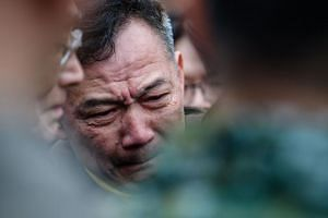 A Hualien resident cries as he speaks with Taiwan's President Tsai Ing-wen as she visits the rescue operations at the Yun Tsui building, which is badly damaged and leaning at a precarious angle, in the Taiwanese city of Hualien on February 8, 2018, a