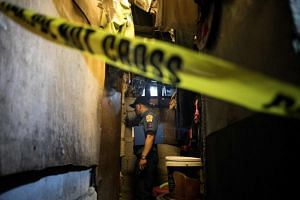 A policeman at the scene where an alleged drug user lies dead in a slum area in Manila after unidentified assailants killed him on Dec 8, 2017.