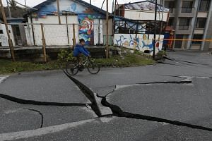 A resident cycles past a damaged street in Hualien, Taiwan, on Feb 8, 2018, after a magnitude 6.4 earthquake hit the city on Feb 6, 2018.