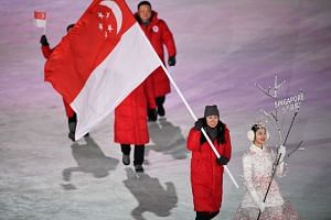Cheyenne Goh of Singapore carries the national flag during the opening ceremony of the Pyeongchang Winter Olympics.