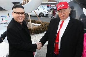 Foreigners posing as US President Donald Trump and North Korean leader Kim Jong Un shake hands in Pyeongchang on Feb 9, 2018.