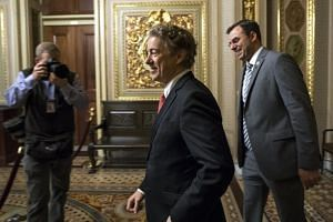 Republican Senator from Kentucky Rand Paul (centre) and Republican Representative from Michigan Justin Amash (right) walk to the Senate floor as budget negotiations continue in the US Capitol in Washington, DC, on Feb 8, 2018.