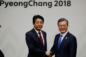South Korea's President Moon Jae In (right) shakes hands with Japan's Prime Minister Shinzo Abe during their meeting in Pyeongchang on Feb 9, 2018.