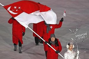 Cheyenne Goh carrying the Singapore national flag yesterday at the Winter Olympics opening ceremony in Pyeongchang. Behind her are chef de mission Tan Paey Fern, coach Chun Lee Kyung, and team manager Antony Lee.