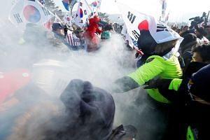 """Police (in green) try to stop demonstrators during an anti-North Korea protest in Pyeongchang yesterday. Seoul is hoping this Winter Olympics will be a """"Peace Olympics"""", though Washington and other parties are concerned that the games may be exploite"""