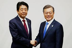 Japanese Prime Minister Shinzo Abe (left) meeting South Korean President Moon Jae In in Pyeongchang yesterday, ahead of the opening ceremony for the Pyeongchang Winter Olympics.