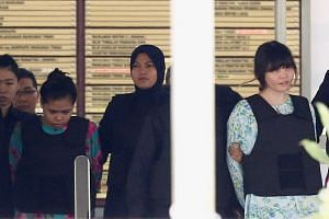 Suspects Doan Thi Huong (right) and Siti Aisyah, on trial for the killing of Kim Jong Nam, being escorted out of Shah Alam High Court in Kuala Lumpur on Oct 3, 2017.