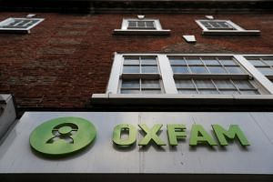 A sign is seen above a branch of Oxfam, in London, Britain on Feb 12, 2018.