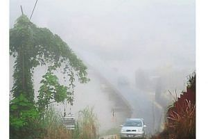 Vehicles emerging from the gloom as thick fog shrouds Gua Musang in Kelantan.