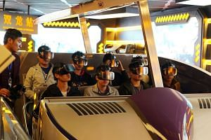 Staff wearing virtual-reality goggles inspecting the attraction Fly Over Guizhou at Oriental Science Fiction Valley theme park in Guiyang, Guizhou province, China, in November last year.