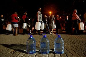 People queue to collect water from a spring in the Newlands suburb as fears over the city's water crisis grow in Cape Town, South Africa, on Jan 25, 2018.